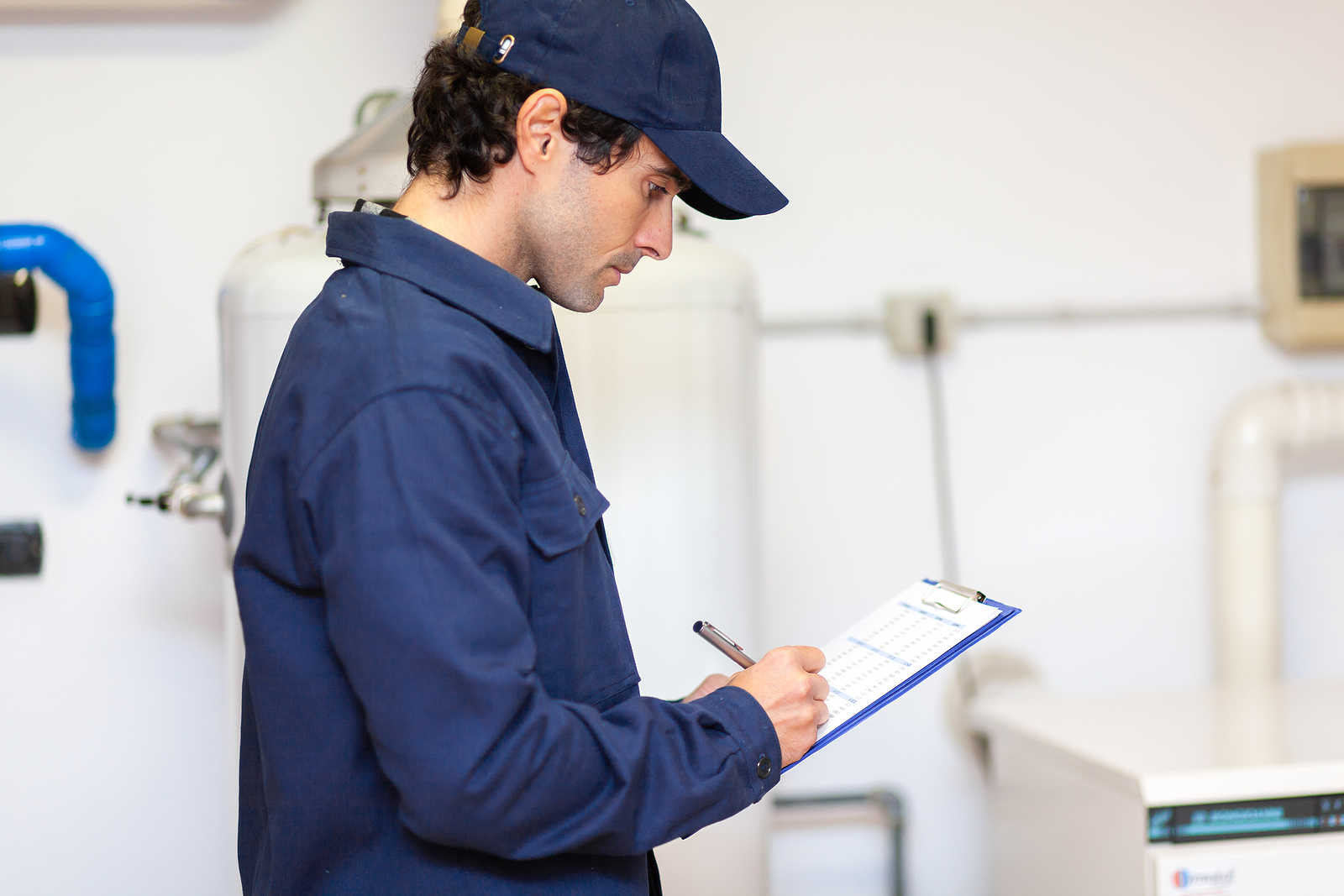 Technician servicing a hot water cylinder installation