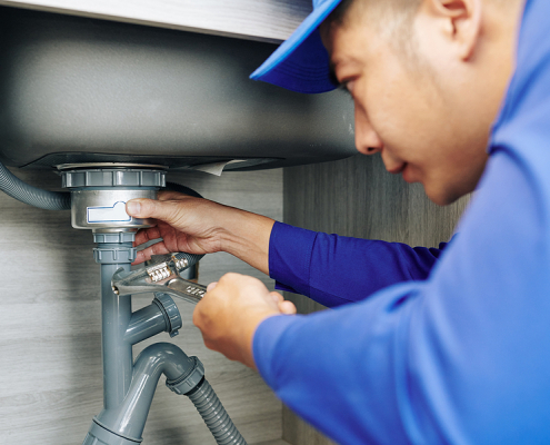 Plumber in Wellington using a wrench to repair a leaky drain