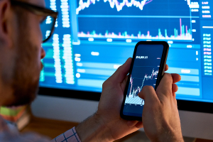 Businessman trader checking trading graphs on his phone